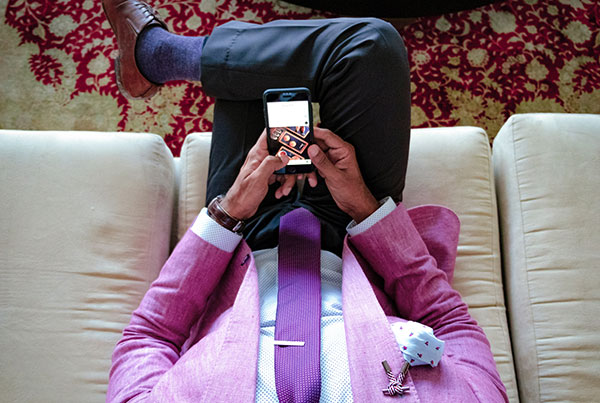 man-in-suit-looking-at-phone